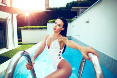 性感的女人泳装在游泳池边摆姿势