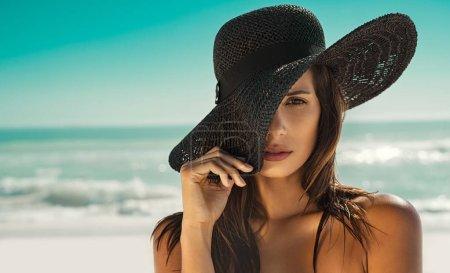 沙滩上戴草帽的时尚女人_高清图片_邑石网