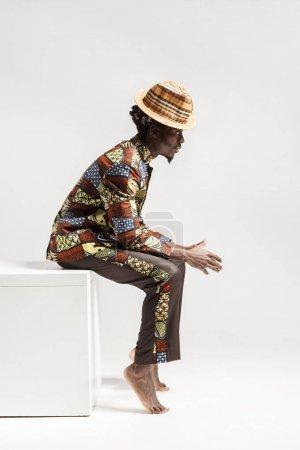 英俊的非洲裔美国男子穿着服装在国家孔戈风格的侧面观看在白色背景上独立的立方体上_高清图片_邑石网
