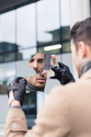美丽的年轻人看着自己在破碎的镜子
