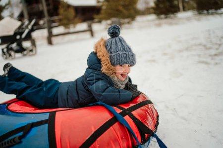 笑着的男孩,一边玩着充气雪管,一边在魔法公园里滑行,一边看着摄像机 _高清图片_邑石网