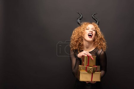 laughing woman in maleficent costume holding presents for halloween on black