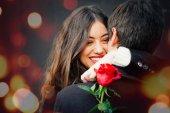 幸福的情侣在爱与玫瑰拥抱在街上