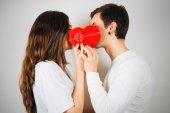 年轻的情侣约吻背后的心形礼品盒