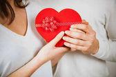 一对夫妇手捧着一个红色的心形礼品盒