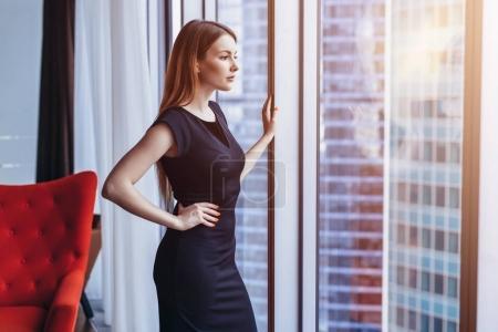 富有魅力的女人思考站在窗口欣赏她的阁楼公寓的城市景观
