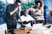 Young team of coworkers making great work discussion in modern office.Bearded man talking with account director and creative manager.Business people meeting concept.Horizontal, blurred background.