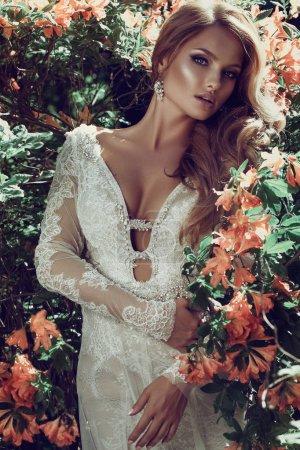 魅力肖像美丽的性感时尚的金发碧眼的年轻女子模型与完美的清洁皮肤附近的夏季花卉。美丽的新娘