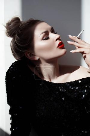 一个美丽的年轻女人谁吐出烟雾的时尚肖像