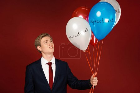 emotional man holding balloons with impeachment lettering on red background