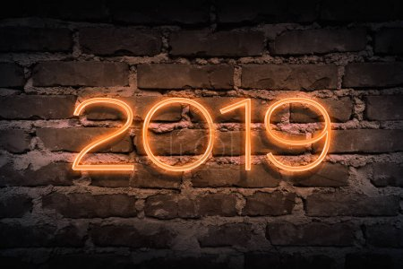 Upcoming 2019 year as neon sign on brickwall pattern as backgoun
