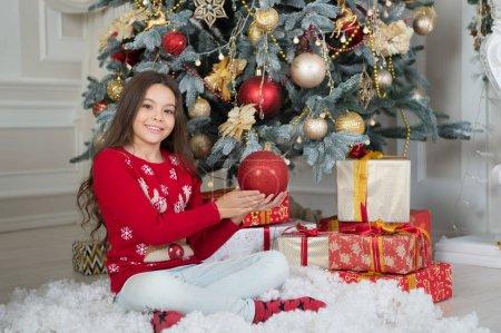 我完美的寒假 在圣诞树附近的小女孩。 孩子们在家里庆祝圣诞节。 冬天的传统 礼品店的概念。 可爱的孩子穿着圣诞毛衣。 圣诞装饰_高清图片_邑石网
