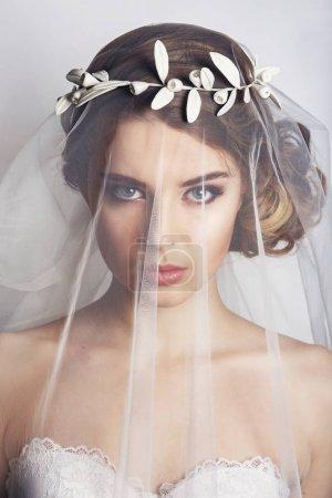 与时尚婚礼发型-白色背景上的美丽新娘。年轻的华丽新娘特写肖像。婚礼。工作室拍摄。美丽的新娘画像带在她脸上的面纱