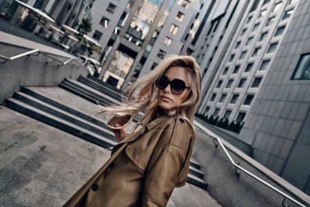fashionable attractive blonde woman holding coffee cup while walking outdoors in city near office building