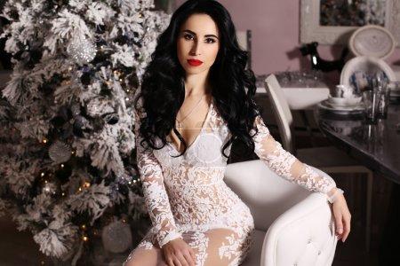 构成在装饰圣诞树旁边的黑头发的性感女人