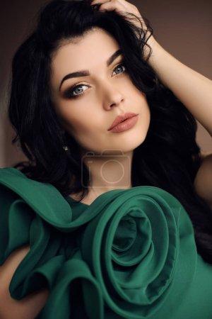 优雅的绿色连衣裙的黑发华丽性感的女孩