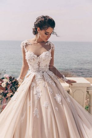 时尚的照片美丽的女人与深色的头发在豪华婚纱摆在户外