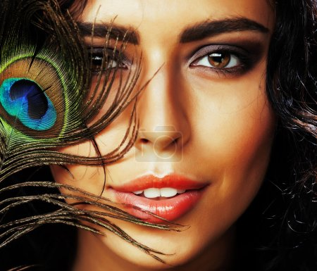 young sensitive brunette woman with peacock feather eyes close u