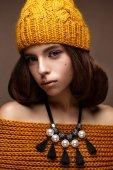美丽的女孩,在她的头和一条项链,在她脖子上的珍珠针织帽子。温柔的化妆与黄金的嘴唇模型。美丽的脸