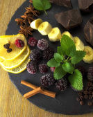 Exposition close up of fresh organic fruit and chocolate, half of lemon, sliced banana, mint leaf, cranberry, blackberry and coffee grape on black background,  rock board, wooden table, healthy food.