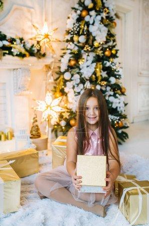 圣诞期间,身穿粉色衣服、头戴礼品盒的快乐微笑的小女孩坐在枞树旁_高清图片_邑石网