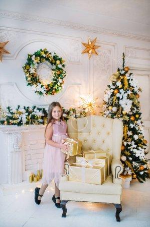 新年前夕,身穿粉色连衣裙的小女孩站在圣诞树旁的扶手椅上._高清图片_邑石网