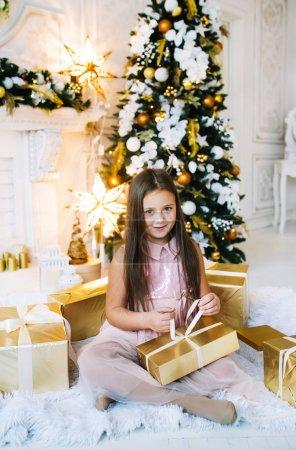身穿粉色衣服的快乐女孩坐在圣诞树旁的地板上,手里拿着金礼品盒_高清图片_邑石网