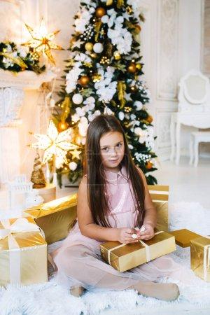 小女孩坐在圣诞树旁的地板上,手里拿着金礼品盒_高清图片_邑石网