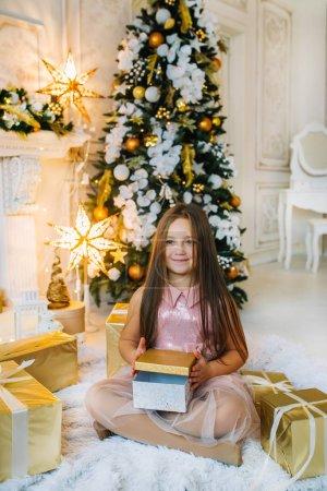小孩坐在圣诞树旁的地板上,手里拿着礼品盒_高清图片_邑石网
