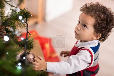 可爱迷人的男孩看着圣诞树