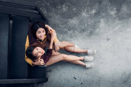 Two female lesbian lgbt couple sitting at black rooftop stair  h