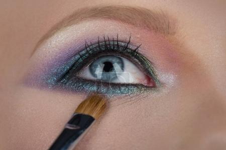化妆的眼睛。女性蓝眼睛特写。美丽的化妆品为脸, 女人诱人的外观。刷蓝色和粉红色的阴影。学生以美丽的颜色、眉毛和性感的女性秀丽_高清图片_邑石网