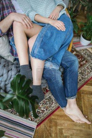 年轻的时髦夫妇在公寓里的旧扶手椅上开心