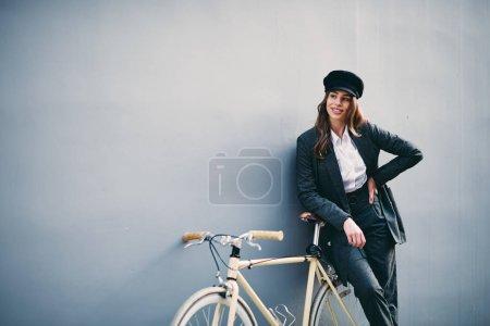 女人摆在她身后的墙黄色自行车前面。手捧帽._高清图片_邑石网