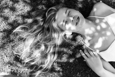 夏天在草地上的可爱的金发碧眼的女人, 黑白