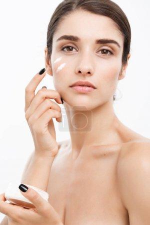 美容青年护肤概念-关闭美丽的白种女人脸肖像涂抹一些奶油她的脸。美丽的水疗模型女孩与完美的新鲜干净的皮肤白色背景