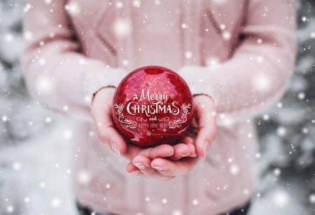 女性的双手托着一个圣诞红球。寒冷冬日里白雪皑皑的丛林中。圣诞快乐和新年快乐主题