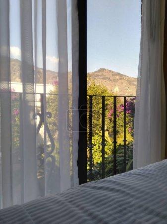 美丽的风景从床通过窗口到庭院和山