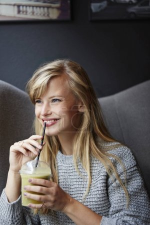 blond woman holding smoothie