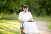 年轻的父亲推着婴儿车在公园