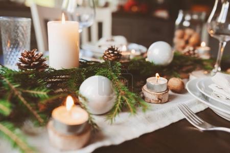 喜庆的圣诞和新年表在斯堪的纳维亚风格自然和白色色调仿古手工制作详细的设置。用餐的地方装饰着松果、 分支机构和蜡烛