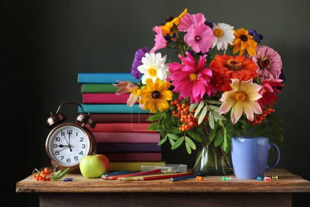 Still life with autumn bouquet, alarm clock and books.