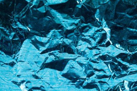 铝箔与紫蓝色着色痕迹。金属弄皱的纸破旧和尘埃。装饰的背景概念。宏观