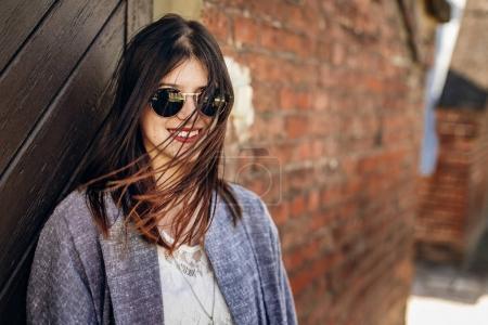 女孩站在旁边的砖墙的太阳镜