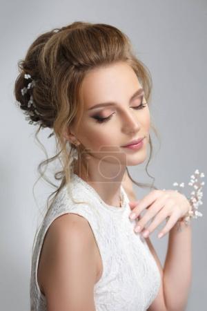漂亮的新娘与美丽的优雅的发型, 在灰色的背景