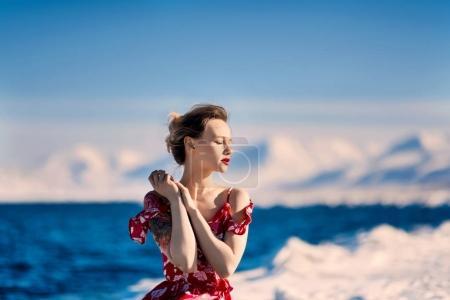 女孩穿着红色山脉斯瓦尔巴群岛在斯匹次卑尔根市朗伊尔城,在阳光明媚的天气背景霜苗条美丽的金发女郎