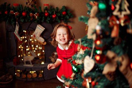 Laughinhg 儿童从圣诞节树后面偷看