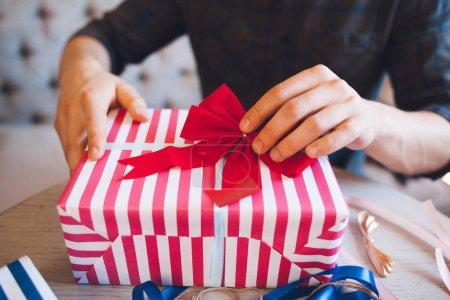 男人装饰着红色蝴蝶结的礼品盒