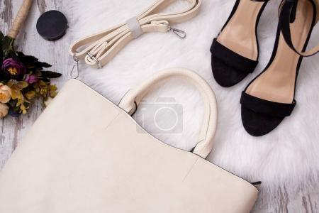 时尚的概念。光包,黑色的鞋子和白色背景上的花朵。顶视图