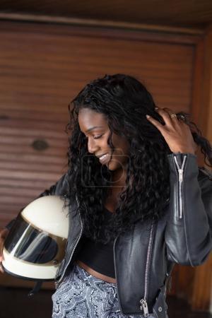 美丽的非洲裔美国妇女黑色皮革摩托车夹克持有老式摩托头盔